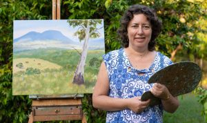 Natalie Barlow showing oil painting of Eumundi landscape scene